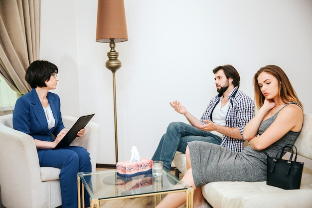 Schönes junges paar sitzt auf sofa. der mensch spricht mit dem psychologen. doktor hört ihm zu. mädchen ist verärgert. Premium Fotos