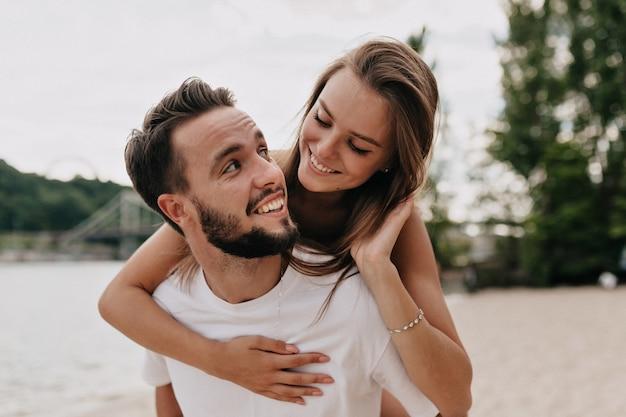 Schönes junges paar spricht und lächelt, während es an einem sonnigen tag am strand spazieren geht Kostenlose Fotos