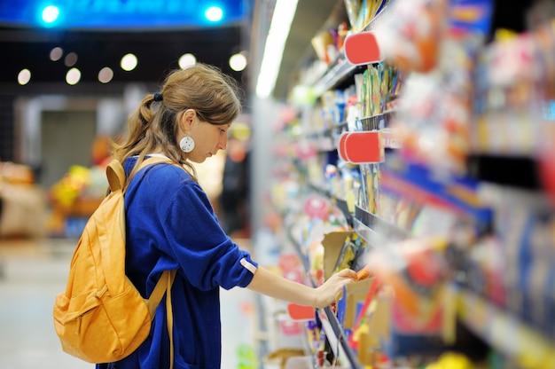 Schönes kaufendes lebensmittel der jungen frau am supermarkt Premium Fotos