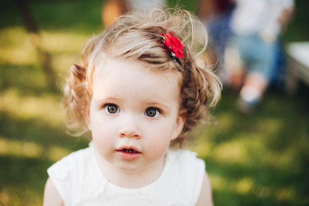 Schönes kaukasisches kleines mädchen mit kurzen welligen blonden haaren im weißen kleid im garten Premium Fotos
