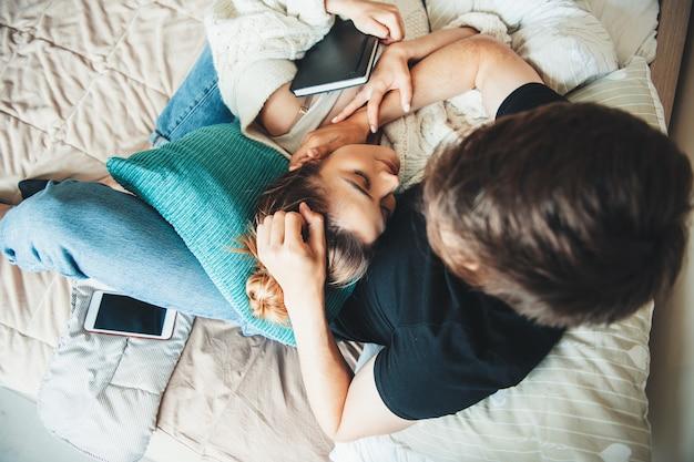 Schönes kaukasisches mädchen mit braunen haaren, die auf ihrem freund im bett liegen, das mit einer steppdecke bedeckt ist und ein buch hält Premium Fotos