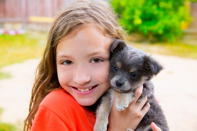 Schönes kindermädchenportrait mit welpenchihuahuahündchen Premium Fotos
