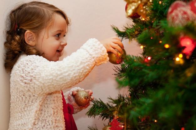 Schönes kleines kind in der nähe von weihnachtsbaum. Premium Fotos