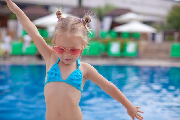 Schönes kleines mädchen breitete ihre arme aus, die nahen swimmingpool stehen Premium Fotos