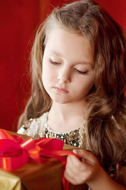 Schönes kleines mädchen, das eine geschenkbox öffnet. weihnachten, neujahr und geburtstagsfeier. Premium Fotos