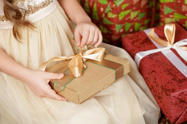 Schönes kleines mädchen, das eine weihnachtsgeschenkbox öffnet. weihnachts- und neujahrsfeier. Premium Fotos