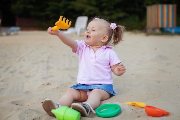 Schönes kleines mädchen, das in der sandkastenstange spielt. das konzept von kindheit und entwicklung. Premium Fotos