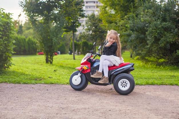 Schönes kleines mädchen, das spaß auf ihrem spielzeugfahrrad im grünen park hat Premium Fotos