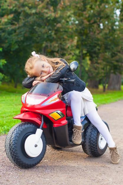 Schönes kleines mädchen, das spaß auf ihrem spielzeugmotorrad hat Premium Fotos