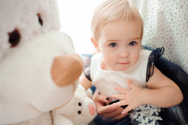 Schönes kleines mädchen mit spielzeug lächelnd in die kamera Premium Fotos