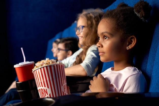 Schönes konzentriertes afrikanisches mädchen mit lustiger frisur, die film im kino sieht. entzückendes kleines weibliches kind, das mit freunden sitzt, popcorn isst und lächelt Premium Fotos