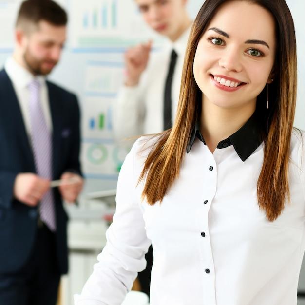 Schönes lächelndes brunetteschreibermädchen am arbeitsplatz Premium Fotos
