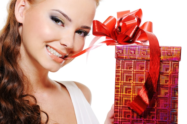 Schönes lächelndes frauengesicht mit einem roten kasten, der band leicht beißt und es durch zähne zeichnet Kostenlose Fotos