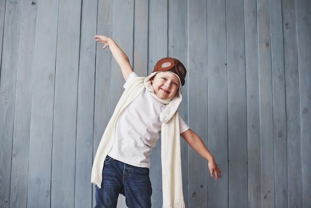 Schönes lächelndes kind im sturzhelm auf einem blauen hintergrund, der mit einem flugzeug spielt. oldtimer-pilot Premium Fotos