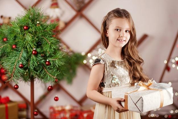 Schönes lächelndes kleines mädchen, das eine weihnachtsgeschenkbox hält. weihnachts- und neujahrsfeier. Premium Fotos