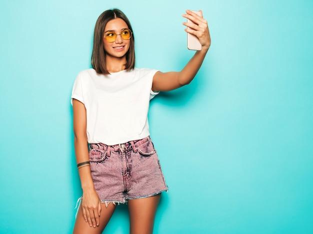 Schönes lächelndes modell gekleidet in sommer hipster kleidung. sexy sorgloses mädchen, das im studio nahe der blauen wand in den jeansshorts aufwirft. trendige und lustige frau, die selfie-selbstporträtfotos auf smartphone nimmt Kostenlose Fotos