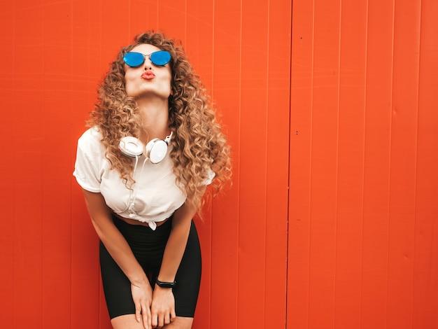 Schönes lächelndes modell mit afro-lockenfrisur gekleidet in sommer-hipster-kleidung. sexy sorgloses mädchen, das nahe rote wand im freien aufwirft. lustige und positive frau, die spaß in der sonnenbrille hat. macht entengesicht Kostenlose Fotos