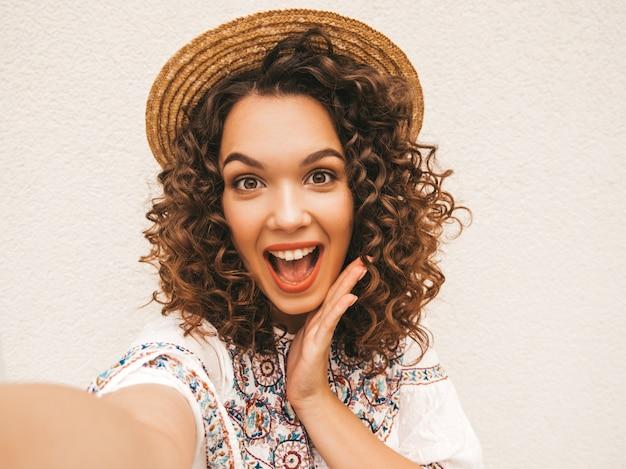Schönes lächelndes modell mit afrolockenfrisur kleidete im weißen kleid des sommerhippies an. Kostenlose Fotos