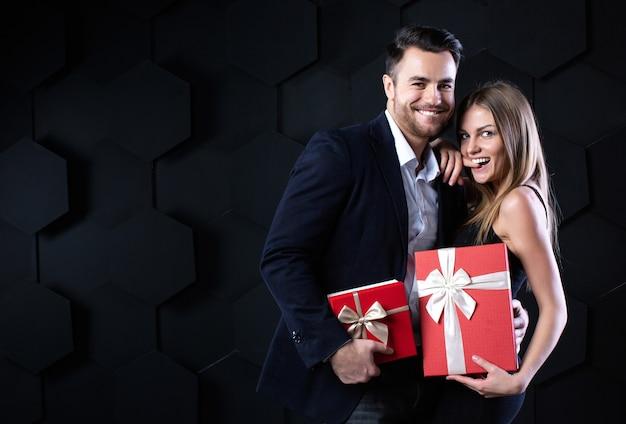 Schönes lächelndes paar mit geschenken. feier und romantisches konzept. Premium Fotos