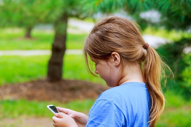 Schönes mädchen, das am telefon spielt Premium Fotos