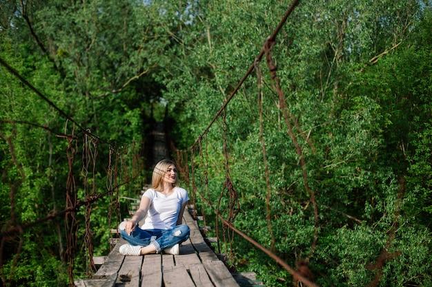 Schönes mädchen, das auf alter holzbrücke sitzt wochenende und ferien im sommerpark. Premium Fotos