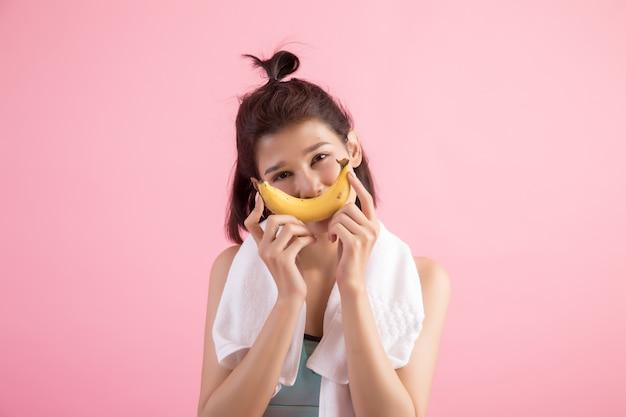 Schönes mädchen, das bananen nach übung isst, um gewicht zu steuern Kostenlose Fotos