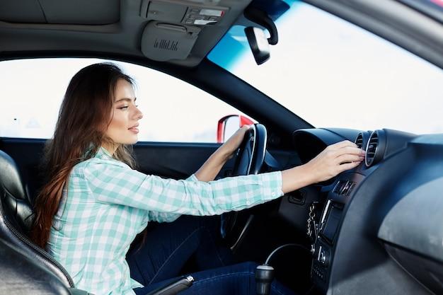 Schönes mädchen, das blaues hemd trägt, das im neuen auto sitzt, glücklich, im verkehr stecken bleibt, musik, porträt, fahrerin hört. Premium Fotos