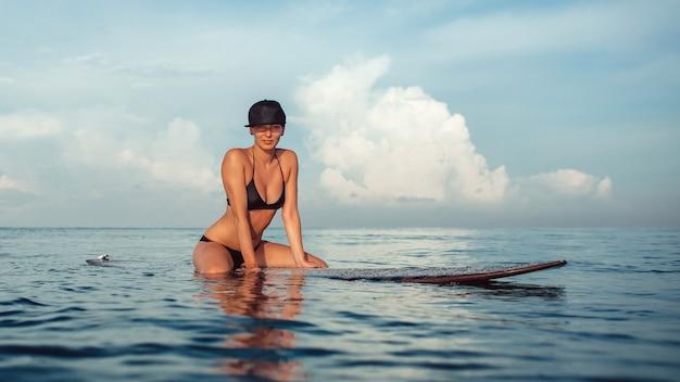 Schönes mädchen, das das sitzen auf einem surfbrett im ozean aufwirft Kostenlose Fotos