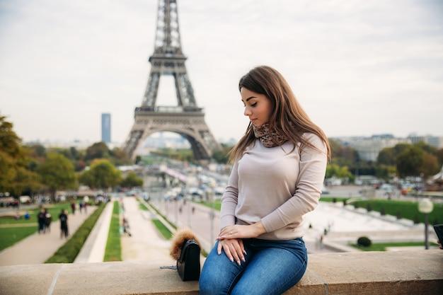 Schönes mädchen, das dem fotografen vor dem hintergrund des eiffelturms aufwirft. herbst Premium Fotos