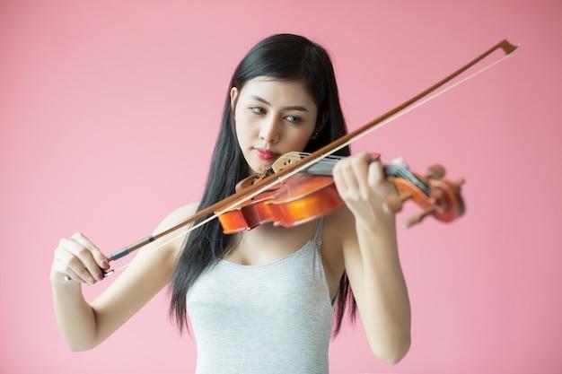 Schönes mädchen, das die violine auf rosa hintergrund spielt Kostenlose Fotos