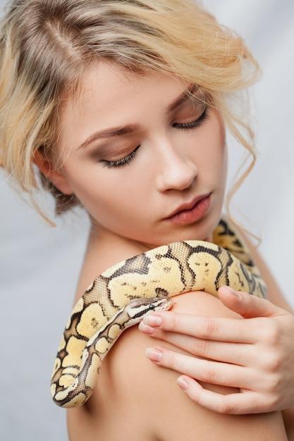 Schönes mädchen, das eine python hält, die sich um ihren körper wickelt Kostenlose Fotos