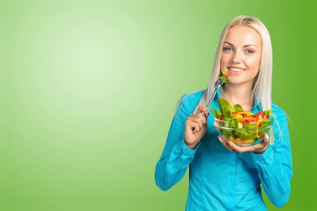 Schönes mädchen, das einen salat isst Premium Fotos