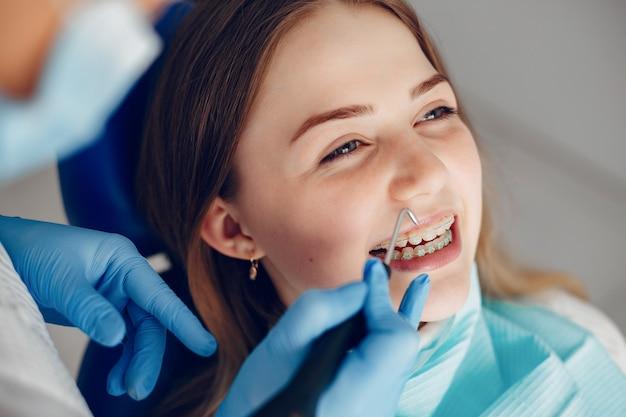 Schönes mädchen, das im büro des zahnarztes sitzt Kostenlose Fotos