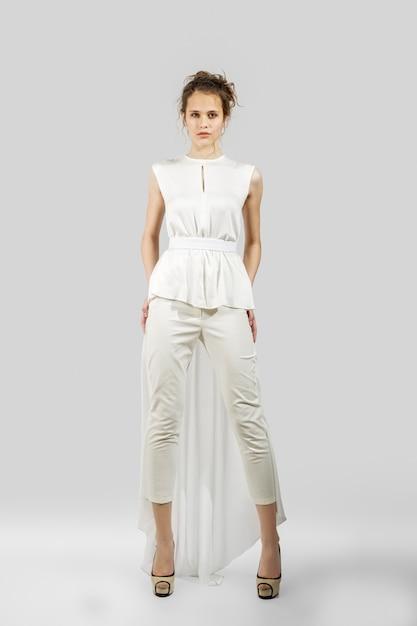 Schönes mädchen, das in den hosen und in der bluse aufwirft. ganzaufnahme des mode-modells. Premium Fotos