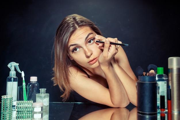 Schönes mädchen, das in den spiegel schaut und kosmetik mit einem großen pinsel anwendet. Kostenlose Fotos