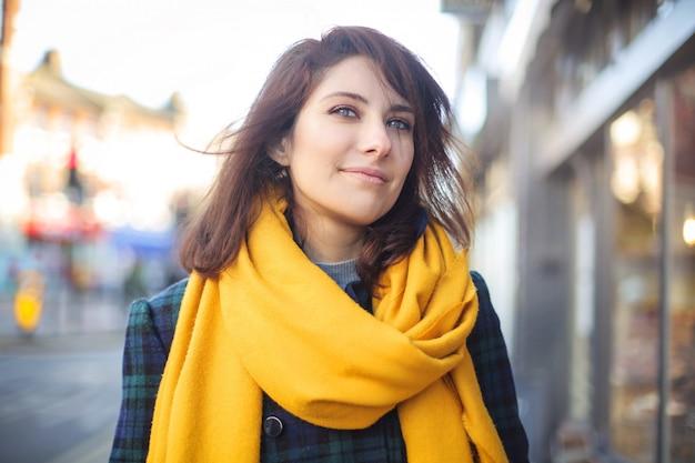 Schönes mädchen, das in die straße, einen gelben schal tragend geht Premium Fotos