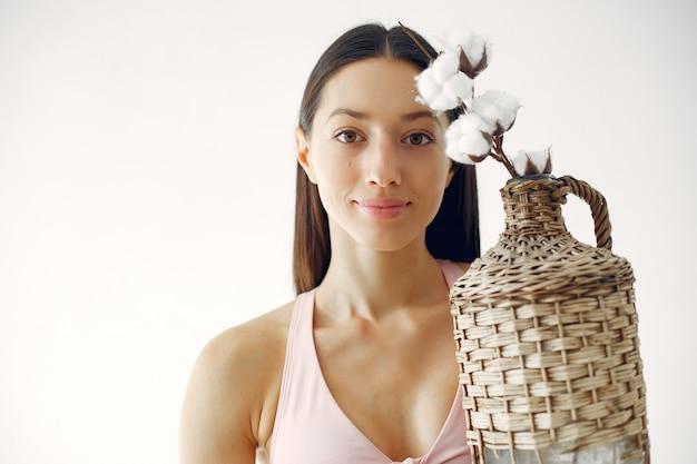 Schönes mädchen, das in einem studio mit baumwollblumen steht Kostenlose Fotos