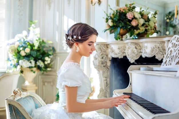Schönes mädchen, das klavier spielt, in einem schönen kleid im inneren Premium Fotos