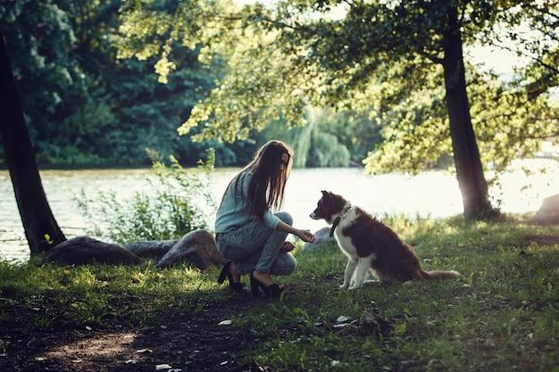 Schönes mädchen, das mit einem hund spielt Premium Fotos