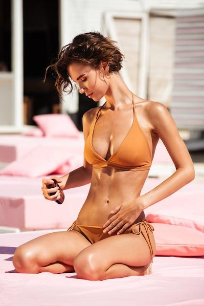 Schönes mädchen im bikini, das auf strandbett mit körperölflasche in der hand sitzt. porträt der jungen dame im beige badeanzug beim sonnenbaden am strand. hübsches mädchen, das sonnenöl auf ihrem körper für sonnenbräune am strand schmiert Premium Fotos