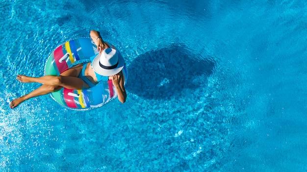 Schönes mädchen im hut in der draufsicht der swimmingpoolluft von oben, junge frau entspannt sich und schwimmt auf aufblasbarem ringdonut und hat spaß im wasser auf familienurlaub, tropisches ferienzentrum Premium Fotos