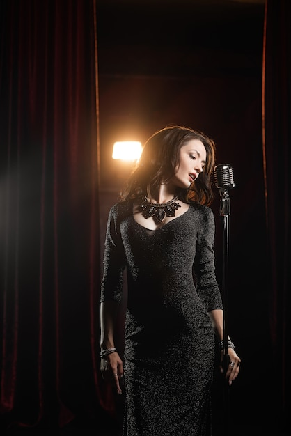 Schönes mädchen im schwarzen kleid singend im mikrofon im konzertsaal Premium Fotos