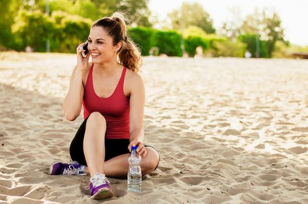 Schönes mädchen im sport kleidet unter verwendung eines smartphone und des lächelns beim stillstehen auf dem strand nach training. Premium Fotos