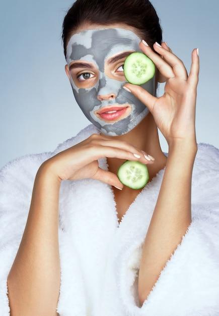 Schönes mädchen im weißen bademantel und mit maske aus lehm Premium Fotos