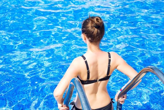 Schönes mädchen in einem badeanzug kommt in den pool Premium Fotos