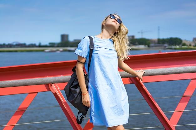 Schönes mädchen in einem blauen kleid posiert auf der brücke Kostenlose Fotos