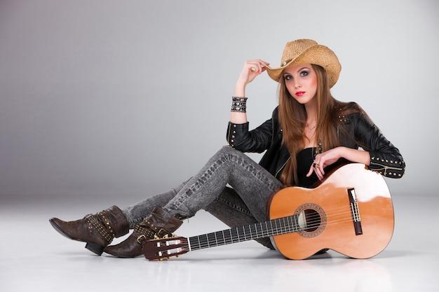 Schönes mädchen in einem cowboyhut und in einer akustikgitarre. Kostenlose Fotos