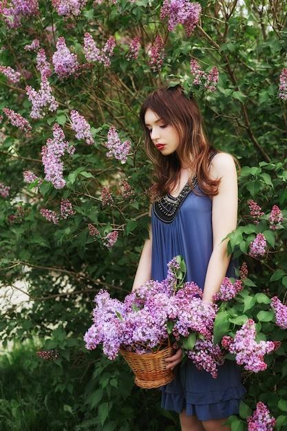 Schönes mädchen in einem kleid, das in bush von fliedern aufwirft Premium Fotos