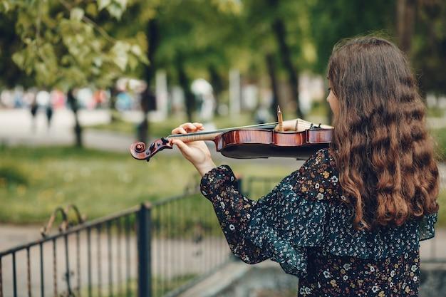Schönes mädchen in einem sommerpark mit einer violine Kostenlose Fotos