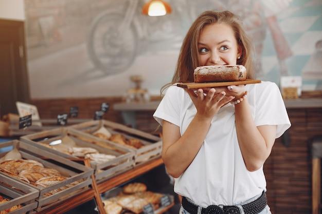 Schönes mädchen kauft brötchen in der bäckerei Kostenlose Fotos